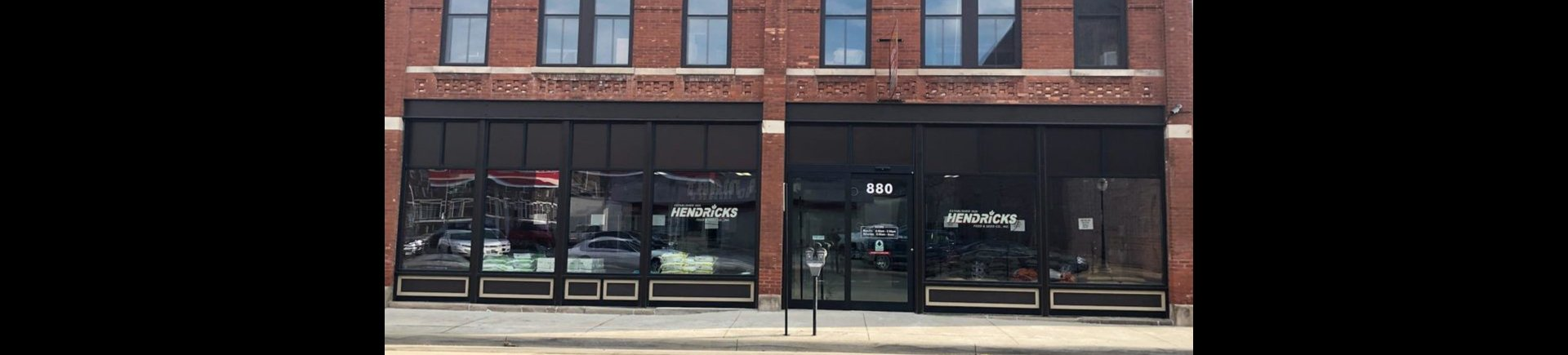 Photo of the outside of Hendricks. The store front is red brick with big windows and black window casings. There is a parking meter in front of the door.