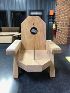 Photo of wooden 'squirrel chair' with rounded back and screw through the center to attach corn to.