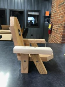 Photo of side view of wooden 'squirrel chair' shaped like an Adirondack chair.