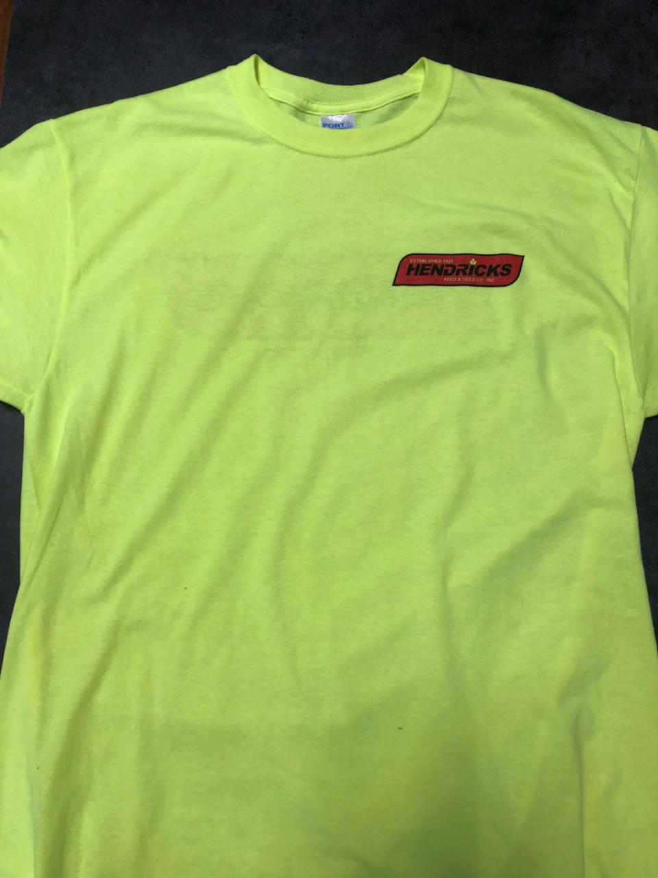 Photo of Hendricks Feed T-shirt. The shirt is yellow with the red Hendricks logo across the front left breast. Written in black and yellow on the red is '(yellow) Estabished 1929, (black) Hendricks, (yellow) Feed & Seed Co., Inc.' is in the banner and 'Dubuque, Iowa' is below the banner.