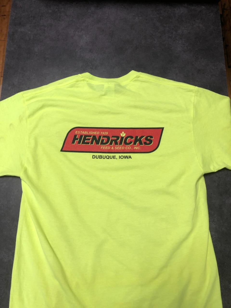 Photo of Hendricks Feed T-shirt. The shirt is yellow with the red Hendricks logo across the front. Written in black and yellow on the red is '(yellow) Estabished 1929, (black) Hendricks, (yellow) Feed & Seed Co., Inc.' is in the banner and 'Dubuque, Iowa' is below the banner.